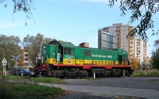 Szara jesień, szare bloki i kolorowa lokomotywa