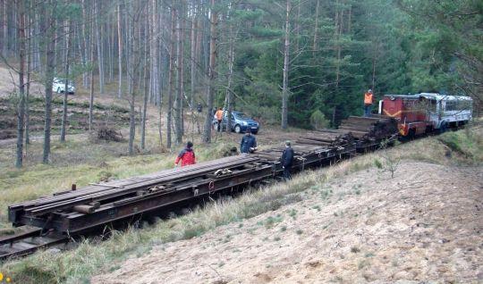 Transportery wąskotorowe z szynami i podkładami w podmanowskim lesie