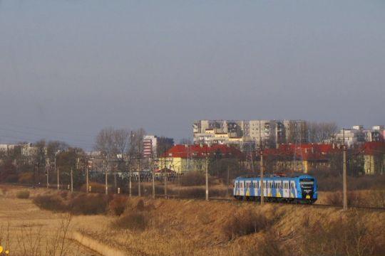 """""""ALicja"""" na tle osiedla Ogrody w Kołobrzegu"""